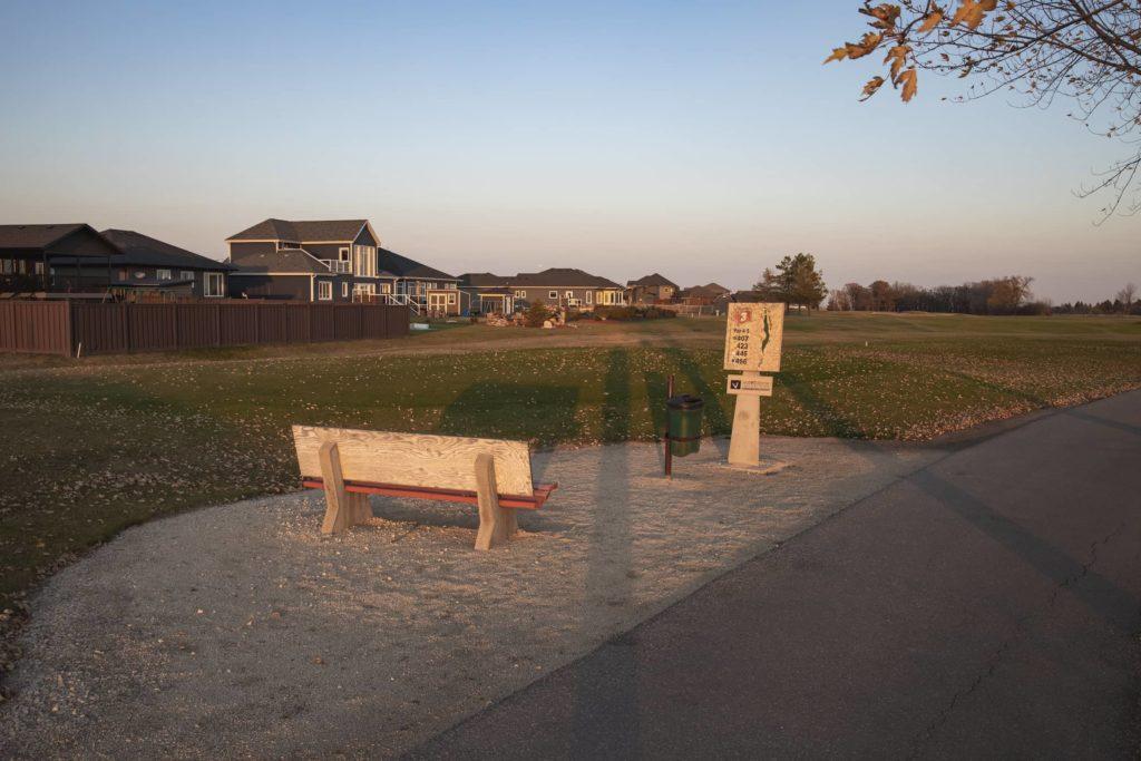 A bench along a golf course path