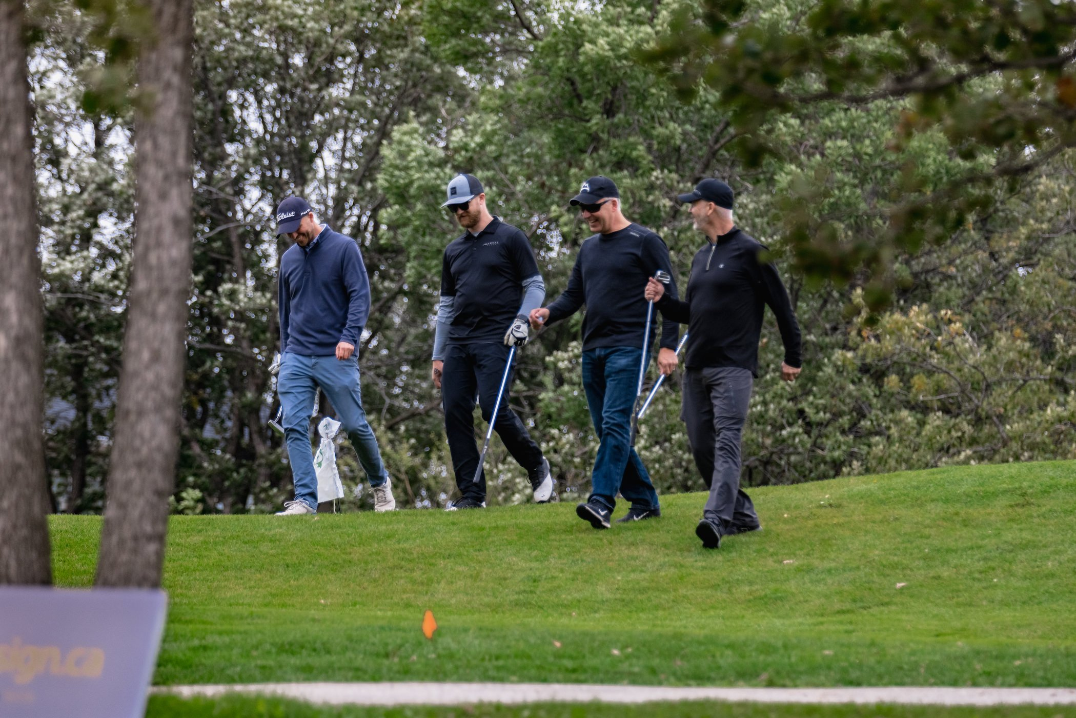 group of men smiling as they walk down the golf course